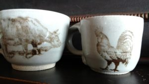 silkscreened cow and a roster on white ceramic mugs
