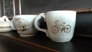 silkscreened cow and bike on ceramic mugs