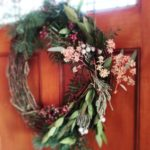 handmade holiday wreath featuring pepper berries and bay leaves